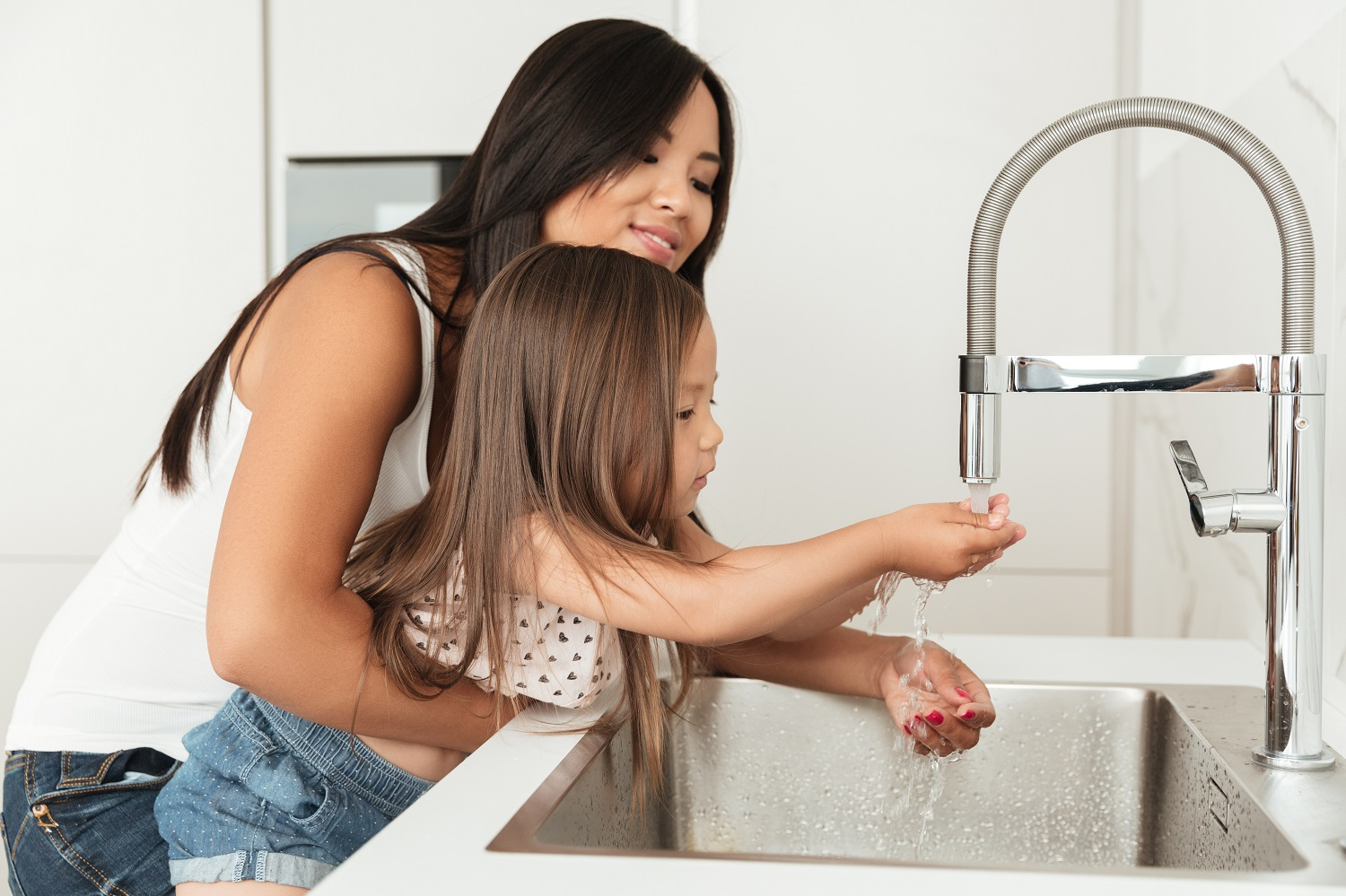 Young asian mother helping her daughter to wash hands