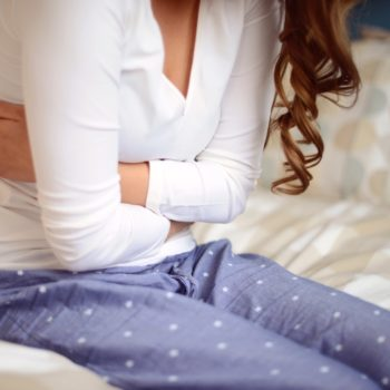 young woman sitting in the bedroom on a bed and holding her stomach, abdominal pain